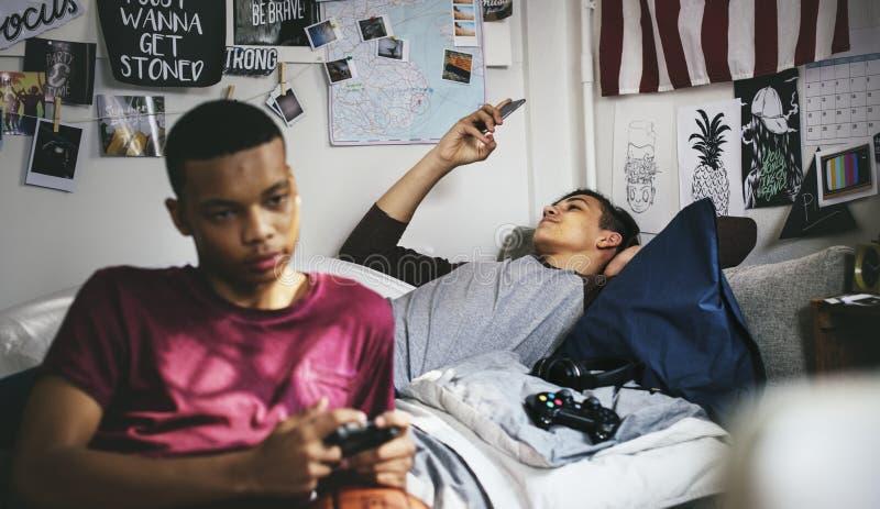 停留在卧室的十几岁的男孩打一个电子游戏和使用智能手机 免版税图库摄影