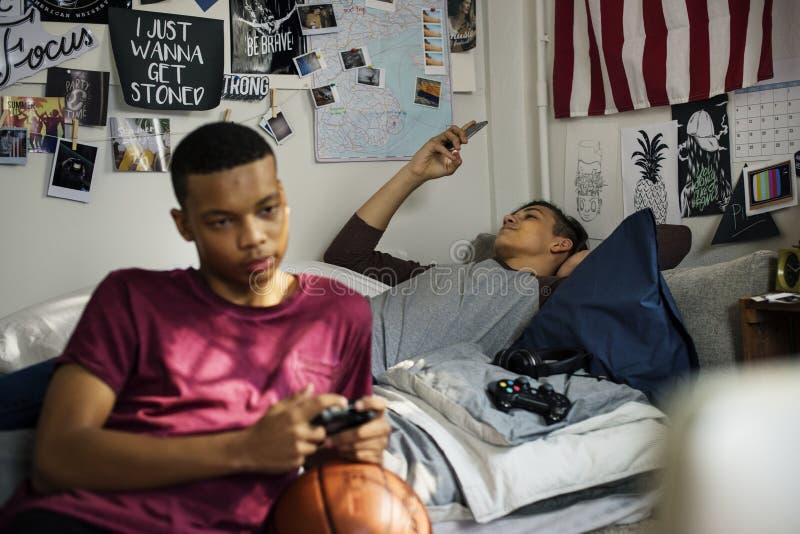 停留在卧室的十几岁的男孩打一个电子游戏和使用智能手机 免版税库存照片