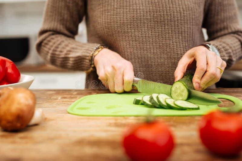 停留在厨房里和砍沙拉的准确妇女成份 免版税库存照片