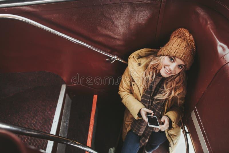 停留在双重甲板公共汽车上的年轻俏丽的妇女 免版税库存图片