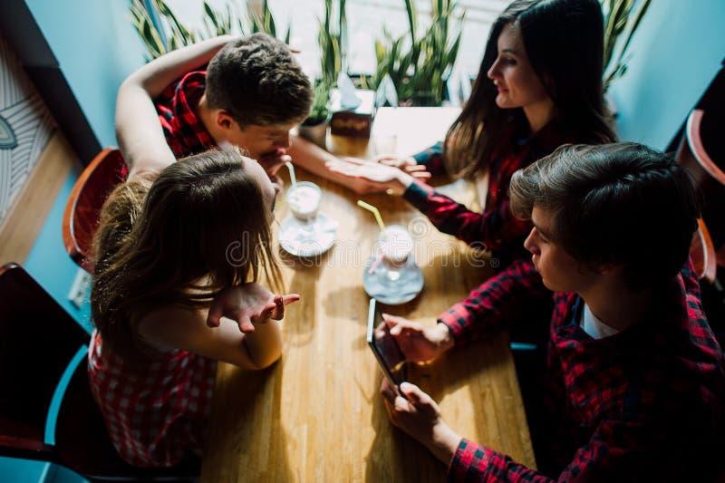 停留在咖啡店的小组年轻朋友 年轻见面在咖啡馆的人和妇女获得乐趣和喝咖啡 Lifesty 免版税图库摄影