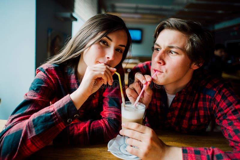 停留在咖啡店的小组年轻朋友 年轻见面在咖啡馆的人和妇女获得乐趣和喝咖啡 Lifesty 库存照片