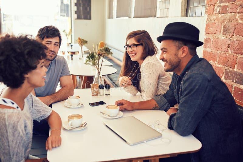 停留在咖啡馆的小组年轻朋友 免版税图库摄影