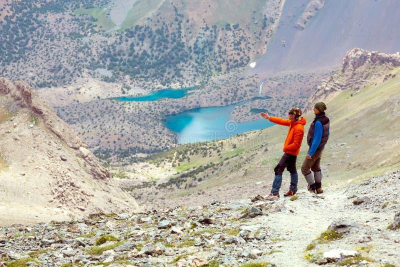停留在多灰尘的足迹的两爬山者 库存照片
