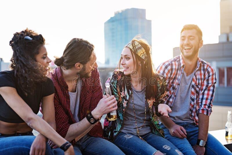 停留在屋顶大阳台的快乐的青年人 免版税库存照片
