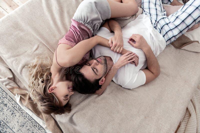 停留在床上的白色衬衫和他逗人喜爱的白肤金发的妻子的英俊的深色头发的年轻人 免版税库存图片