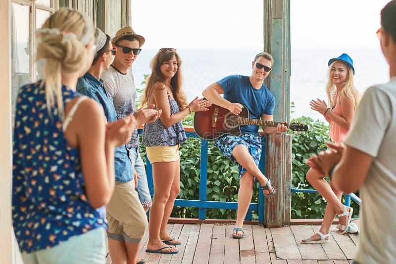 停留在度假的朋友在老木客舱门廊由海,当他们中的一个演奏吉他和其他时 免版税库存图片