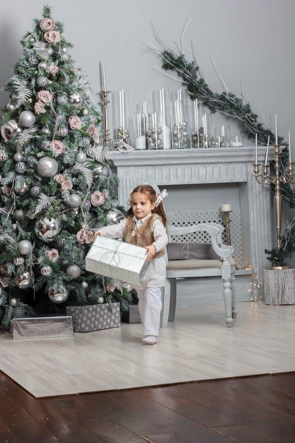 停留在有圣诞树和礼物的屋子的小孩女孩 库存照片