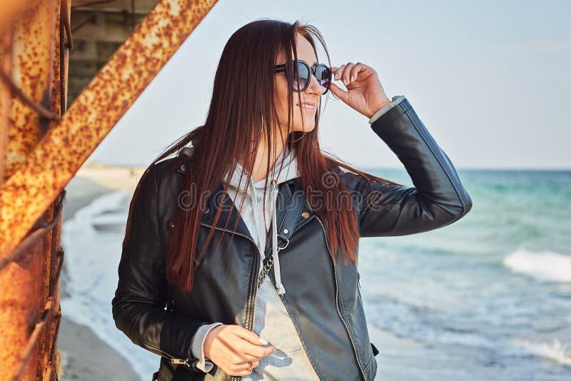 停留在海滩的美丽的年轻红头发人妇女靠近海洋 免版税库存图片