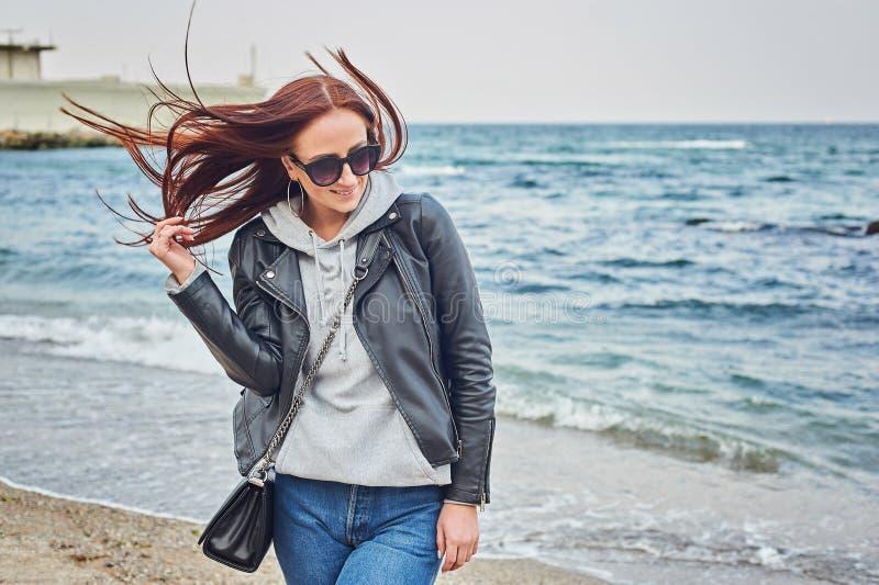 停留在海滩的美丽的年轻红头发人妇女靠近海洋 免版税库存照片