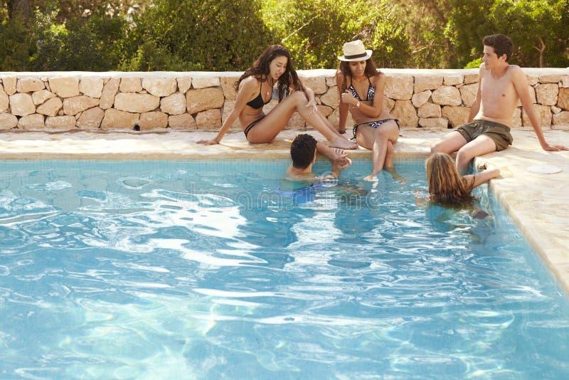 停留在游泳池,伊维萨岛的少年朋友 免版税库存照片