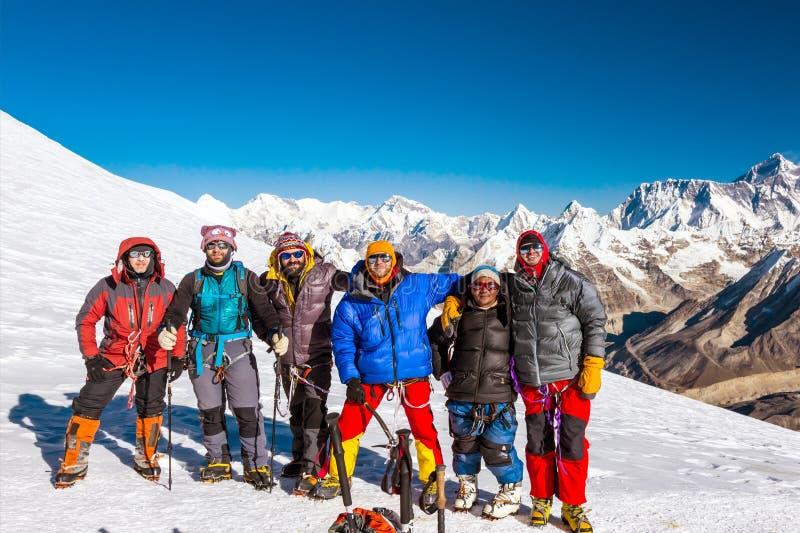 停留在积雪覆盖的喜马拉雅山通行证顶部的小组登山人 免版税库存照片