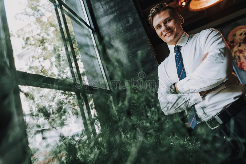 停留在窗口附近的成功的微笑的年轻人 图库摄影