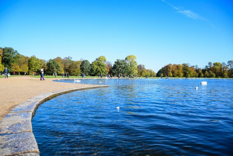 停留在肯辛顿宫前面的一个圆的池塘的游人在伦敦,英国 库存图片