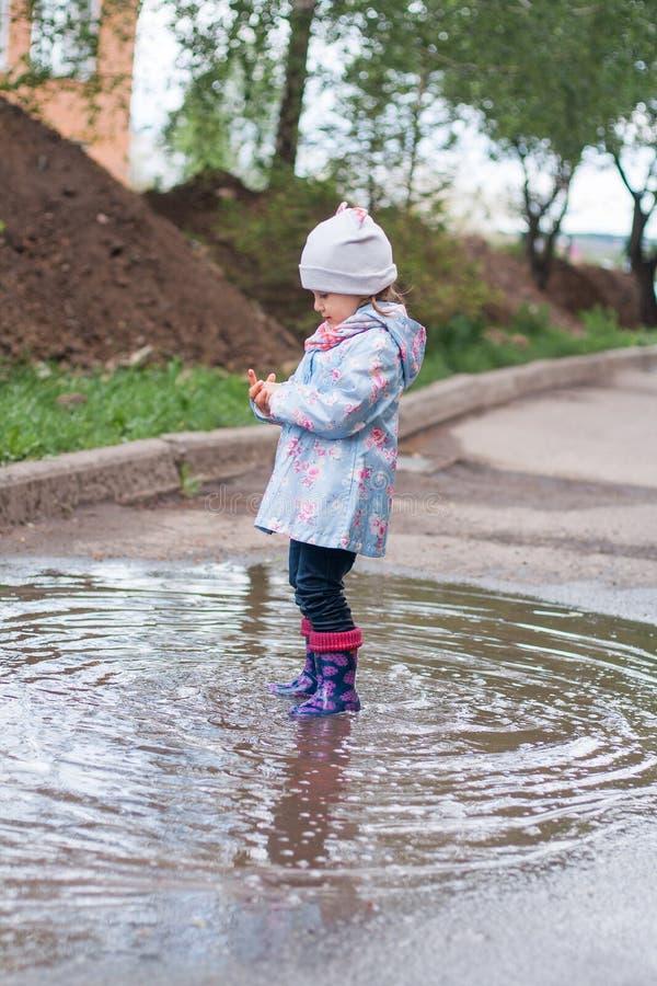 停留在水坑的小女孩 库存照片
