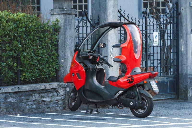 停留红色BMW的滑行车停放在老房子附近 免版税库存照片