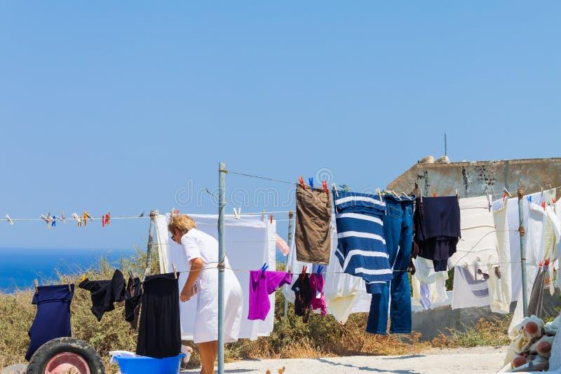 停留衣裳的妇女在Oia村庄在圣托里尼海岛上的烘干 免版税库存照片