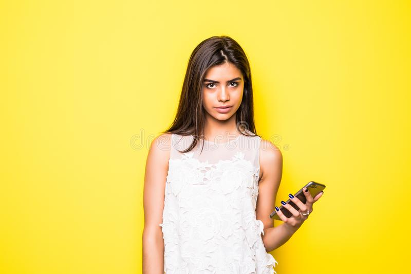 停留连接 看她的手机的愉快的少妇隔绝了黄色墙壁背景 免版税库存图片