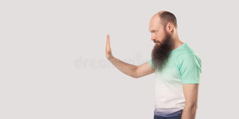 停,等等 中年秃头长须青T恤站立停手头的侧视像 免版税库存图片