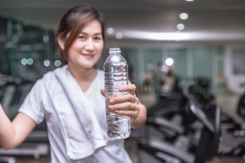 健康亚洲妇女手举行展示瓶与体育俱乐部的饮料水 库存图片