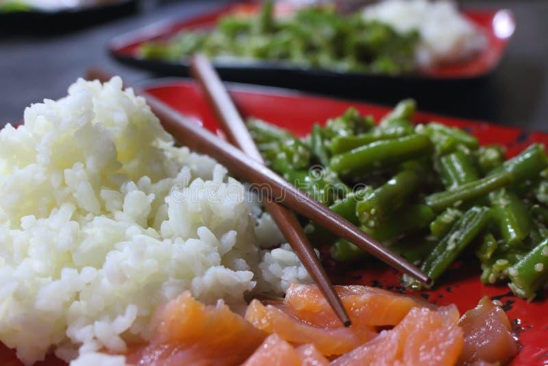 健康亚洲食物:白米、红色鱼三文鱼和青豆在芝麻 与筷子特写镜头的中国烹调 库存照片