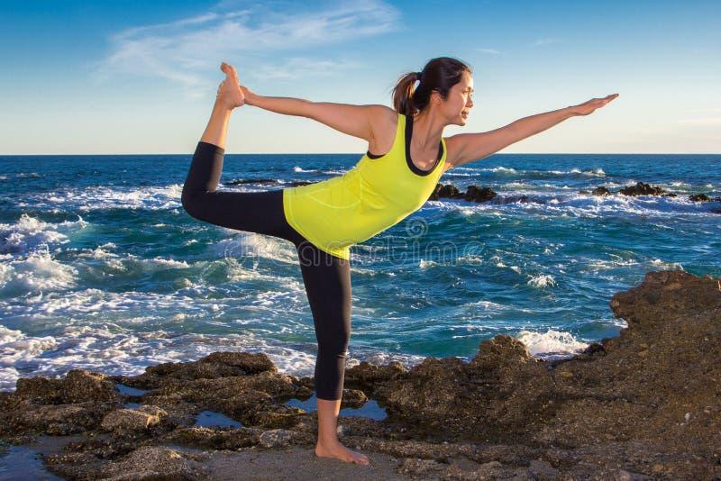 健康亚裔在佩带黄色上面的海滩的女子实践的瑜伽 免版税库存照片