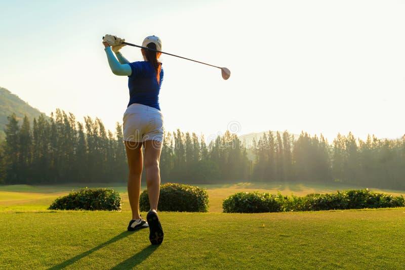 健康体育 做高尔夫球摇摆发球区域在绿色平衡的时间的亚裔运动的女子高尔夫球运动员球员,她据推测行使 免版税库存图片