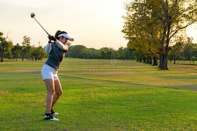 健康体育 做高尔夫球摇摆发球区域在绿色平衡的时间的亚裔运动的女子高尔夫球运动员球员,她据推测行使 库存照片