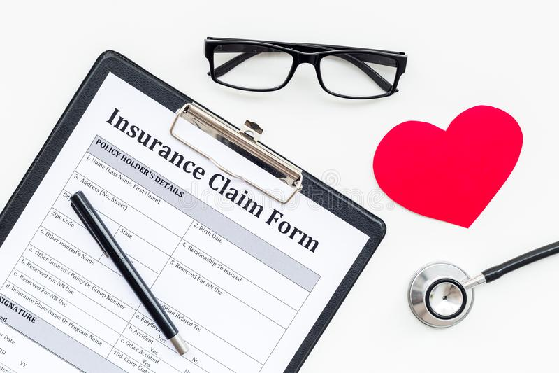 健康保险索赔表为填好  在心脏标志附近的空的在白色背景顶视图的形式和听诊器 免版税库存图片