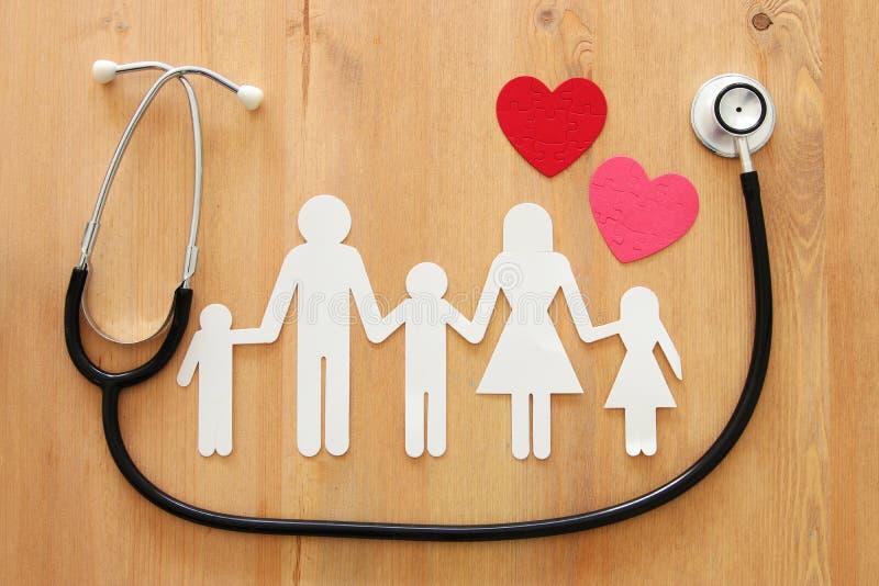 健康保险 听诊器和家庭的概念图象在木桌上 免版税库存图片