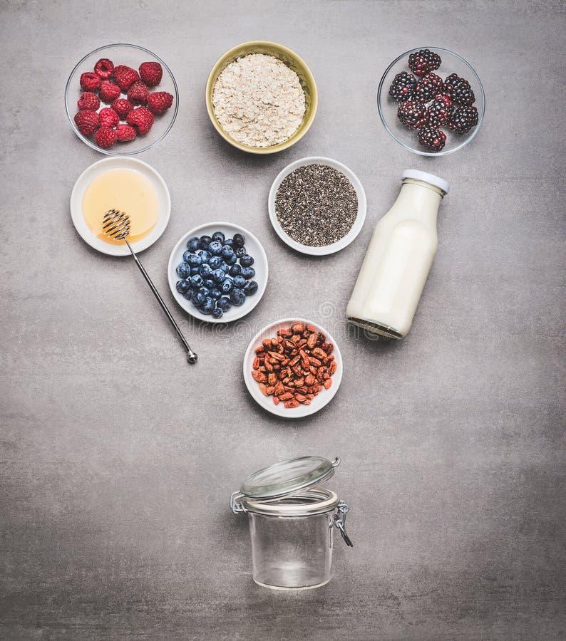健康做用成份的早餐玻璃瓶子:chia种子、goji莓果、燕麦粥、新鲜的莓果、蜂蜜和牛奶或者酸奶 免版税图库摄影