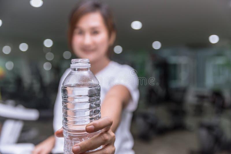 健康健身女孩微笑手举行给水瓶饮用水 免版税图库摄影