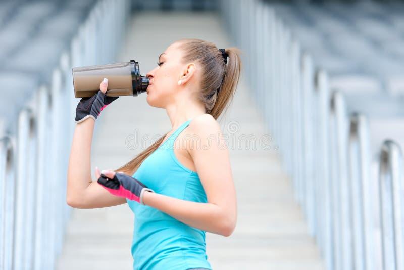 健康健身女孩饮用的蛋白质震动 妇女饮用的体育营养饮料,当解决时 免版税库存照片