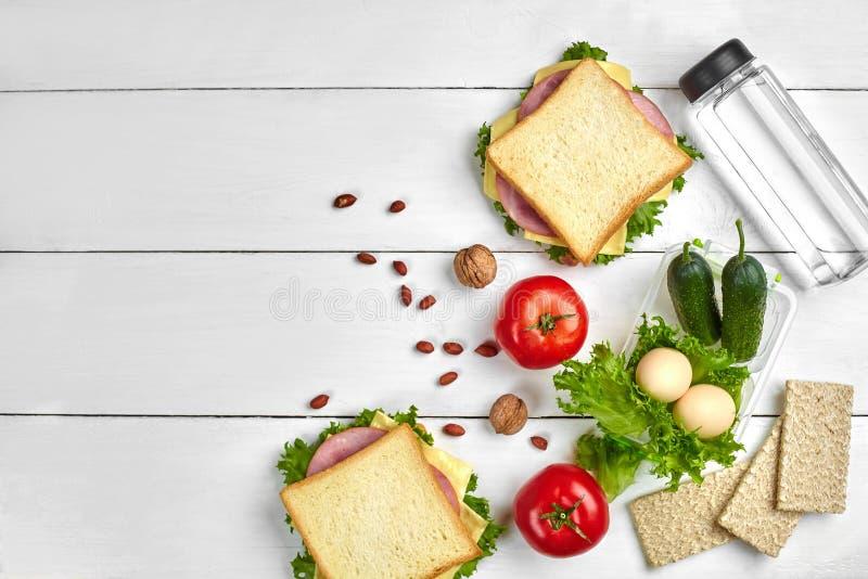 健康午餐盒用三明治、鸡蛋和新鲜蔬菜、在土气木背景的瓶水和坚果 顶层 库存照片