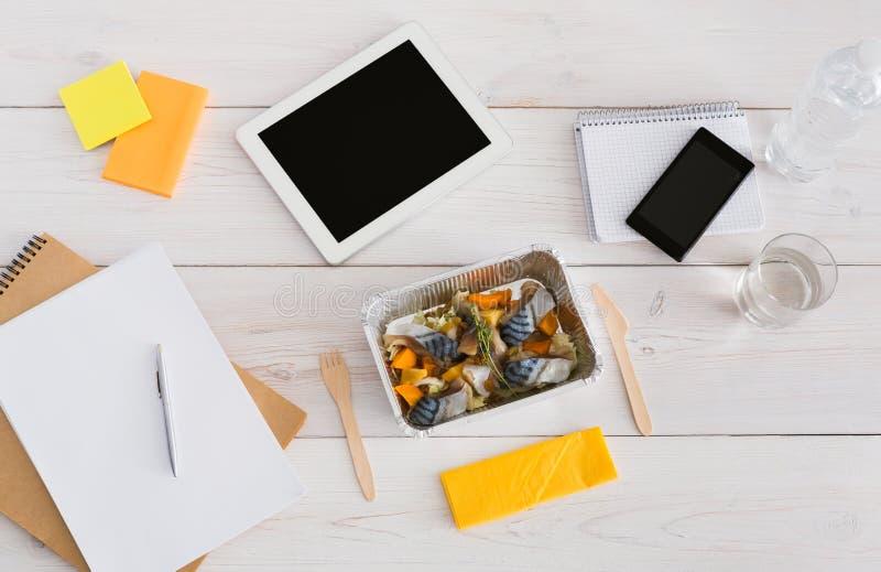 健康午餐箔箱子用在办公室桌上的饮食食物 免版税库存图片