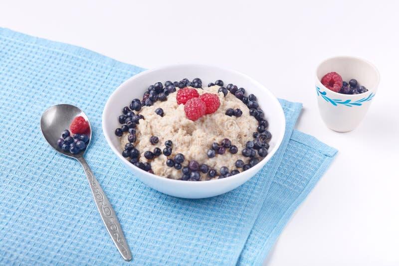 健康可口早餐、燕麦粥用蓝莓和莓顶视图在白色板材在蓝色桌和匙子上 ?? 免版税库存照片