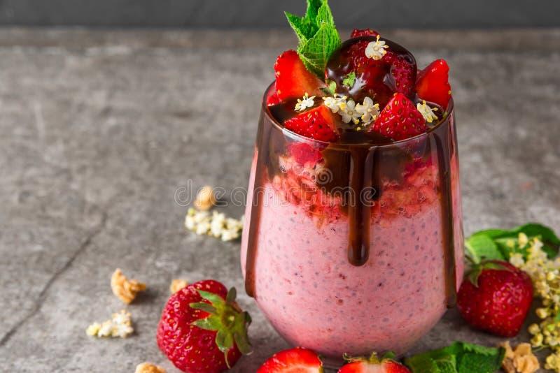 健康可口早餐草莓chia种子布丁用巧克力、新鲜的莓果、格兰诺拉麦片、elderflowers和薄菏 库存照片