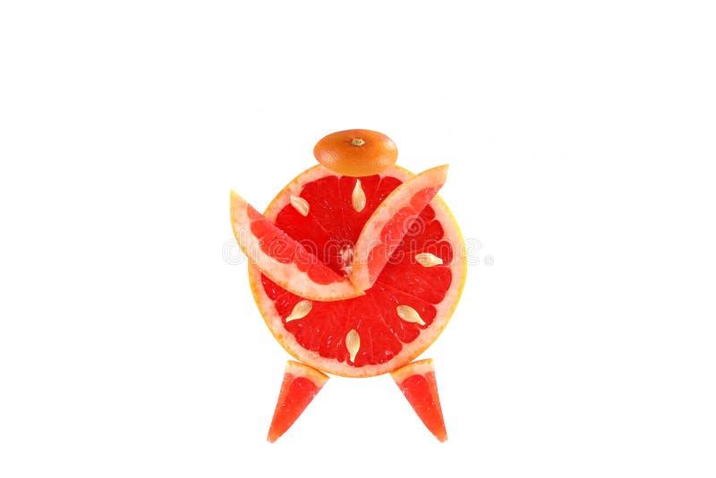 健康吃。滑稽的闹钟被做葡萄柚切片。 库存照片