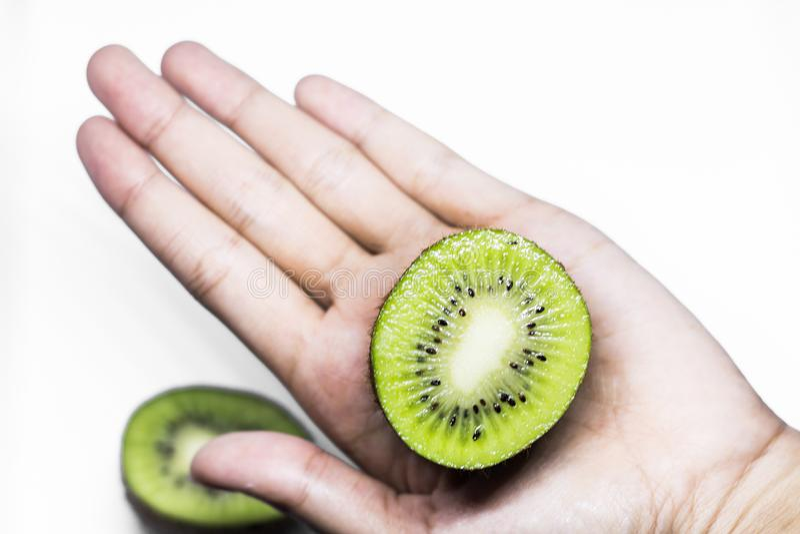 健康吃和饮食题目:拿着一个半猕猴桃的人的手被隔绝在白色背景在演播室 图库摄影