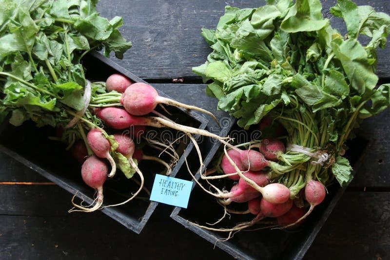 健康吃标记和萝卜在一个木箱在桌上 免版税图库摄影