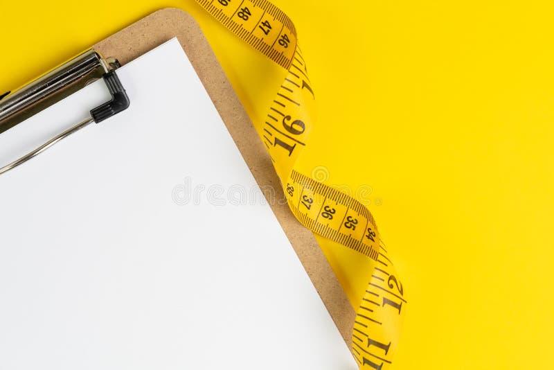 健康吃计划、饮食或者健身计划,在剪贴板的空白的白皮书有在坚实黄色背景的测量的磁带的, 免版税库存照片