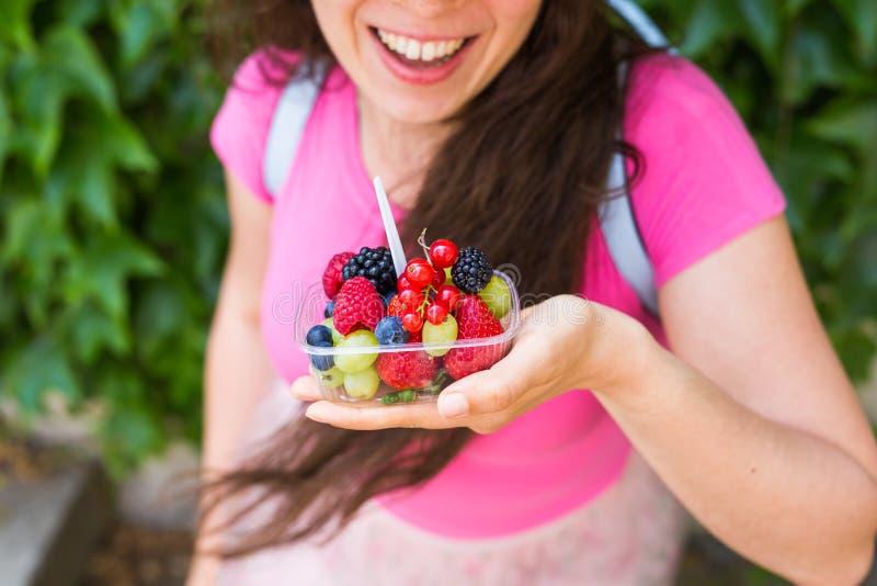 健康吃,节食,素食食物和人概念-接近妇女递拿着莓果室外 免版税库存照片