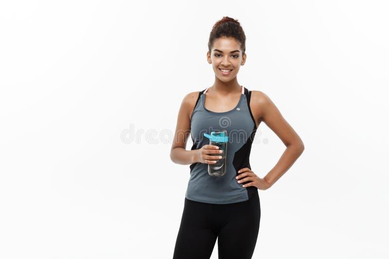 健康和健身概念-体育的美丽的非裔美国人的女孩在锻炼以后给拿着水瓶穿衣 免版税库存图片