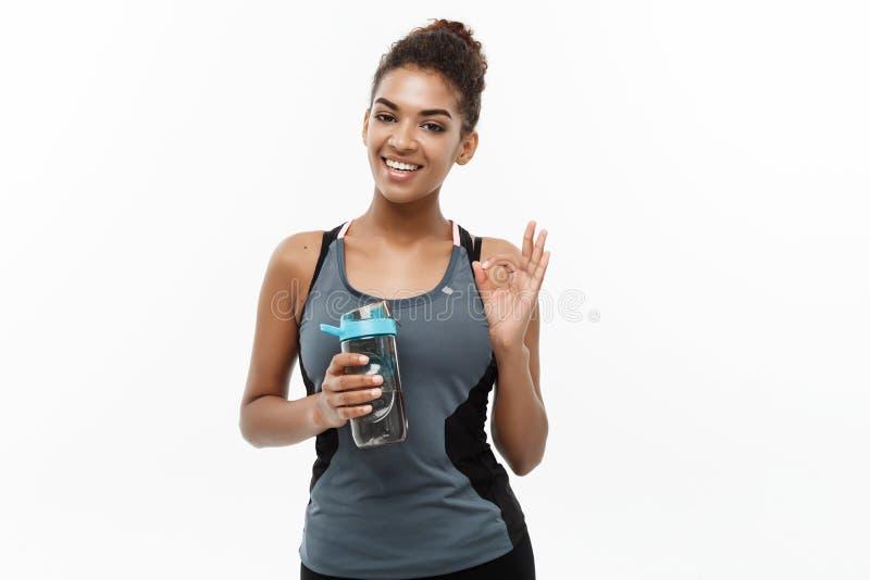 健康和健身概念-体育的美丽的非裔美国人的女孩在锻炼以后给拿着水瓶穿衣 库存图片