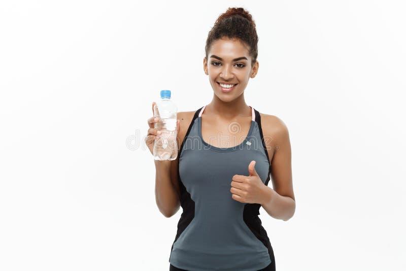 健康和健身概念-体育的美丽的非裔美国人的女孩给以后拿着塑料水瓶穿衣 免版税库存照片