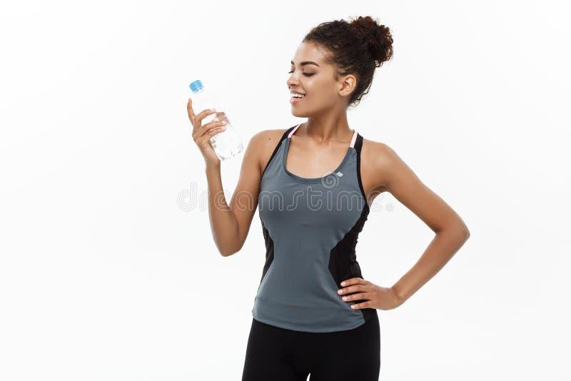 健康和健身概念-体育的美丽的非裔美国人的女孩给以后拿着塑料水瓶穿衣 图库摄影