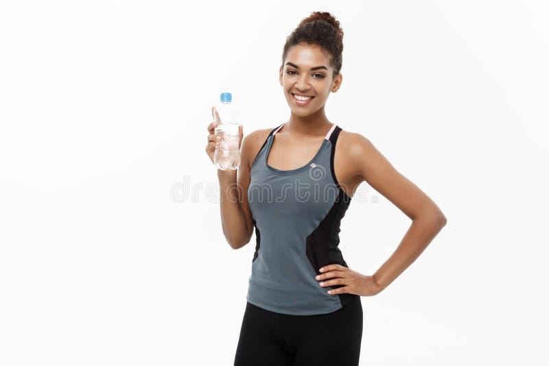 健康和健身概念-体育的美丽的非裔美国人的女孩给以后拿着塑料水瓶穿衣 免版税库存图片