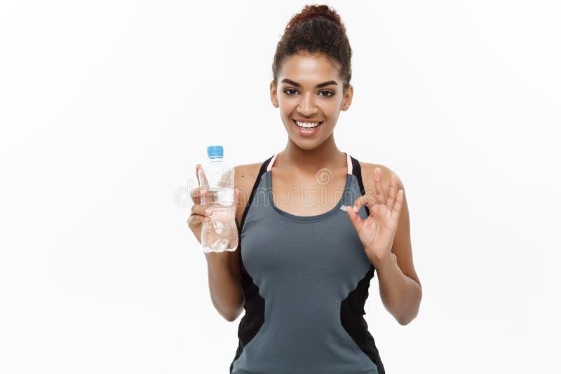 健康和健身概念-体育的美丽的非裔美国人的女孩给以后拿着塑料水瓶穿衣 库存照片