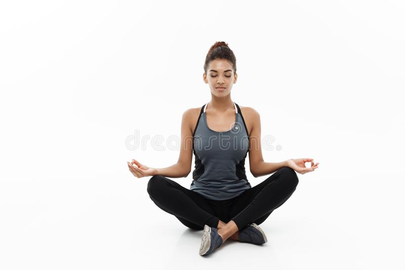 健康和健身概念-做瑜伽和凝思的健身衣物的美丽的美国非洲夫人 隔绝  库存照片