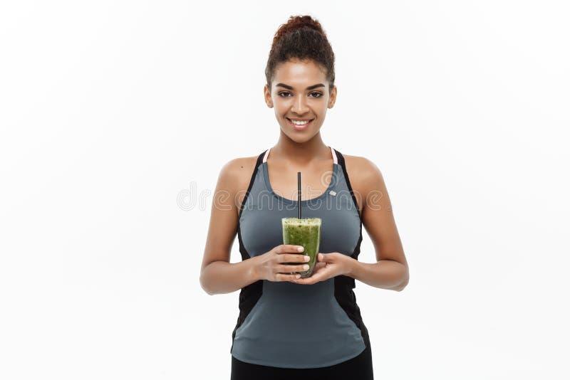 健康和健身概念-健身衣物的美丽的美国非洲夫人喝健康菜饮料的 免版税库存图片